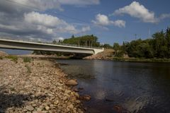 A bridge going over a river with forest on the right hand side. And a rocky beach on the left.  The blue sky contains white clouds, brown, day, green royalty free stock image