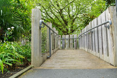 Bridge with hand rails. In the countryside in London at springtime, lush green foliage, flowers and trees with green leaves in the daytime Royalty Free Stock Images