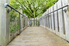 Bridge with hand rails. In the countryside in London at springtime, lush green foliage, flowers and trees with green leaves in the daytime Stock Image