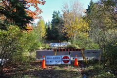 A bridge that has been washed out with cement barricades and orange plastic cones with a do not enter sign along a rural road. A rural scene on Cape Breton Stock Photos