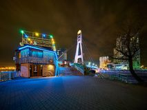 Bridge of Kisses and a restaurant in the winter evening. The embankment is illuminated by street lamps royalty free stock photography
