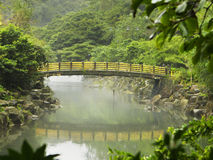 Bridge In Korea. A bridge with yellow railings crosses over a river on Jeju Island in Korea. The bridge is framed by branches in the jungle Royalty Free Stock Photography