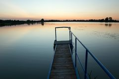 Bridge on the lake and cloudless sky after sunset. Staw, Poland. Bridge made of planks and a metal railing on the lake and cloudless sky after sunset. Staw royalty free stock photo