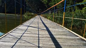 Bridge on the lake. Colourful beauty nature. Bridge on the river. Symmetry in the ordinary life. Forest and plants Stock Photos