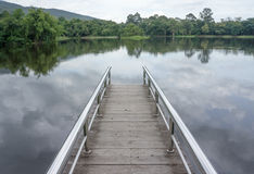 Bridge on the lake. Surround by forest and mountains Stock Image
