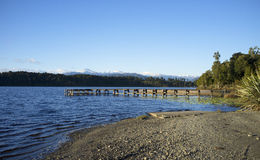 A bridge in a lake. A wooden bridge on a lake under clear blue sky Royalty Free Stock Photography