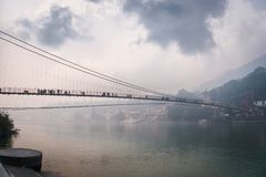 Bridge Lakshman Jhula over the river Ganges in the city of rishies,. India. evening dark landscape. Houses on the high slopes of the Himalayas stock photo
