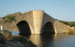 `Bridge of the Laughter` Small, wavy and steep old stone bridge over Mediterranean coast water way Stock Photos