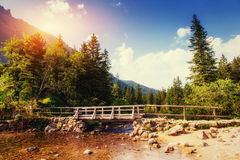 The bridge leading across a river to the mountains Royalty Free Stock Images