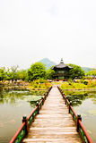 A bridge leading out to a oriental style pagoda Stock Photos