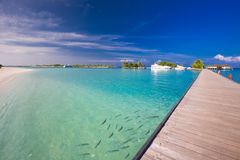 Bridge leading to overwater bungalow in blue lagoon around tropi Royalty Free Stock Photography