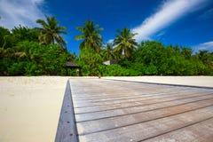Bridge leading to overwater bungalow in blue lagoon around tropi Royalty Free Stock Photos