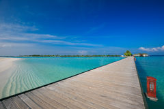 Bridge leading to overwater bungalow in blue lagoon around tropical island in Maldives Stock Images