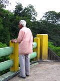 Bridge in Life n' Death. An old begar  stands on a bridge remembering his past life and might be awaiting his death Royalty Free Stock Photo