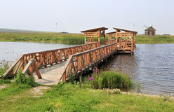 Bridge of love and an old mill. Tourist Complex Siberian Podvorye. Stock Photos