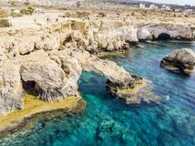 Bridge of Lovers rock formation on the rocky shore of the Mediterranean sea on the island of Cyprus Ayia NAPA. Tourists walk along royalty free stock image