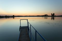 Bridge made of planks and a metal railing on the lake. Staw, Pol. Bridge made of planks and a metal railing on the lake, the horizon and a cloudless sky after stock images