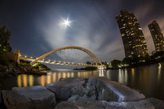 Bridge by Moonlight in Fisheye View. Illuminated arch bridge at night with a harvest moon Stock Photos