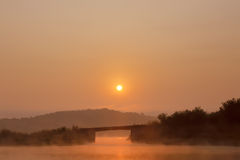 Bridge in the morning fog at sunrise Stock Photos