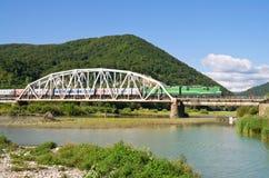 Bridge through mountain river Stock Images