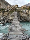 The bridge through mountain small river. Get in the distant Tajik village in the mountains of Badakhshan is possible only on the suspension bridge over the rough Stock Photos