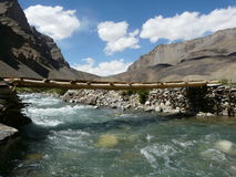 The bridge through mountain small river. The bridge on the mountain river in Gorno-Badakhshan Tajikistan Royalty Free Stock Photo