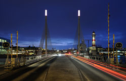 Bridge at night. With cars on the way over and a lighthouse Stock Photo