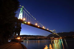 Bridge at night. Lions gate bridge lit up at night with city lights reflecting Stock Image