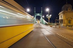 Bridge by night with blurred motion tram Royalty Free Stock Images