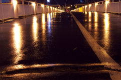 The bridge at night closeup wet asphalt light Stock Image