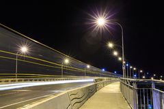 Bridge at night, with light trails streaking across it royalty free stock images