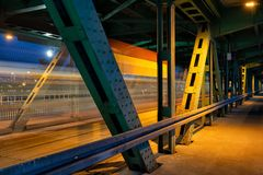 Bridge By Night In Warsaw. Bridge by night with tram light trails behind metal frame in Warsaw, Poland royalty free stock photography