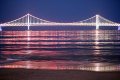 Bridge - Night View. View on a colorfully illuminated suspended bridge and it's reflection in the water. View from Gwangalli Beach in Busan, South Korea Royalty Free Stock Images