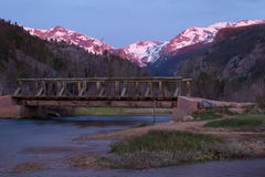 Bridge over The Big Thompson River in Rocky Mountain National pa. The cub lake trailhead foot bridge crosses The Big Thompson River as the mountains glow at royalty free stock image