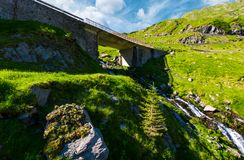 Bridge over the brook in mountains. Beautiful transportation scenery in summer landscape. location Transfagarasan rout of Romania stock images