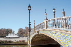 Bridge over canal. Spain's Square, with lamp post and ceramic railing, some fountain are in one side with trees in the background royalty free stock photography