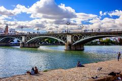 Sunday in Sevilla, Spain. Bridge over the Canal de Alfonso XII with people enjoying the sunday and the autumn sun. Sevilla, Spain Stock Photography