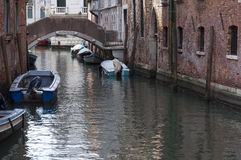 Bridge over a canal, with docked boats, Venice, Italy Stock Photos