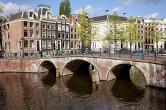 Bridge over Canal and Houses in Amsterdam Stock Images