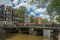Bridge over canal with old buildings, people and cyclists passing by in Amsterdam. Royalty Free Stock Photos