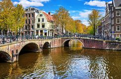 Bridge over channel in Amsterdam Netherlands houses river Amstel. Bridges on the channel in Amsterdam, Netherlands. Traditional dutch Houses under water of royalty free stock image