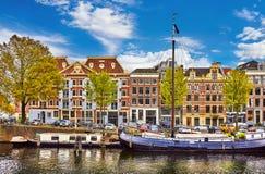 Bridge over channel in Amsterdam Netherlands houses river Amstel landmark old european city spring landscape. Royalty Free Stock Photo