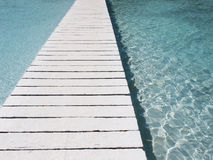 Bridge over clear water. A white bridge over clear pool water Stock Image