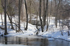 Bridge over Crevice. Little wooden bridge spanning a deep crevice full of water, surrounded by snow, in a forested area Stock Photography