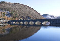 Bridge over the dams at Elan Valley, Powys. A bridge over the reservoir at Elan Valley, with snow capped mountains in the distance Royalty Free Stock Images