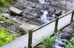 The bridge over the falls. Wooden bridge over the mountain river Stock Photography
