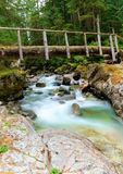 Bridge over forest stream. Wooden bridge over forest stream with rocky banks Royalty Free Stock Photo
