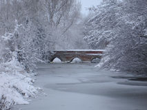 Bridge over frozen river. In a snowy winter landscape Stock Photography