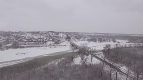 Bridge over a frozen river in winter, aerial photography stock footage