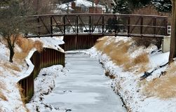 Bridge over frozen stream. Winter scenery. Royalty Free Stock Images